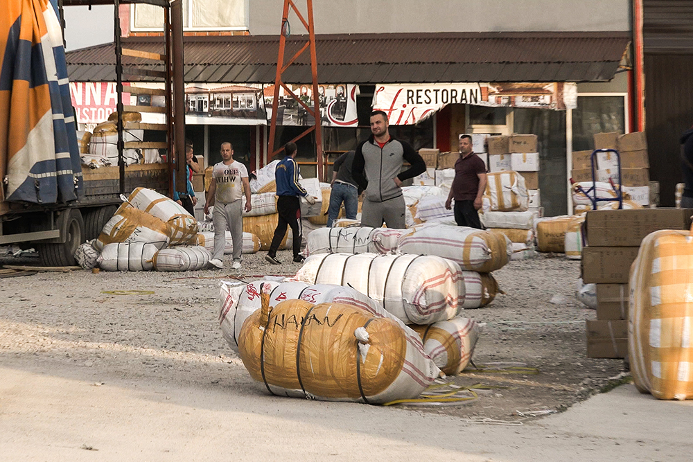 """Market workers unload freshly cleared textiles imported by the company """"Extrablatt"""" (Photo: CIN)"""